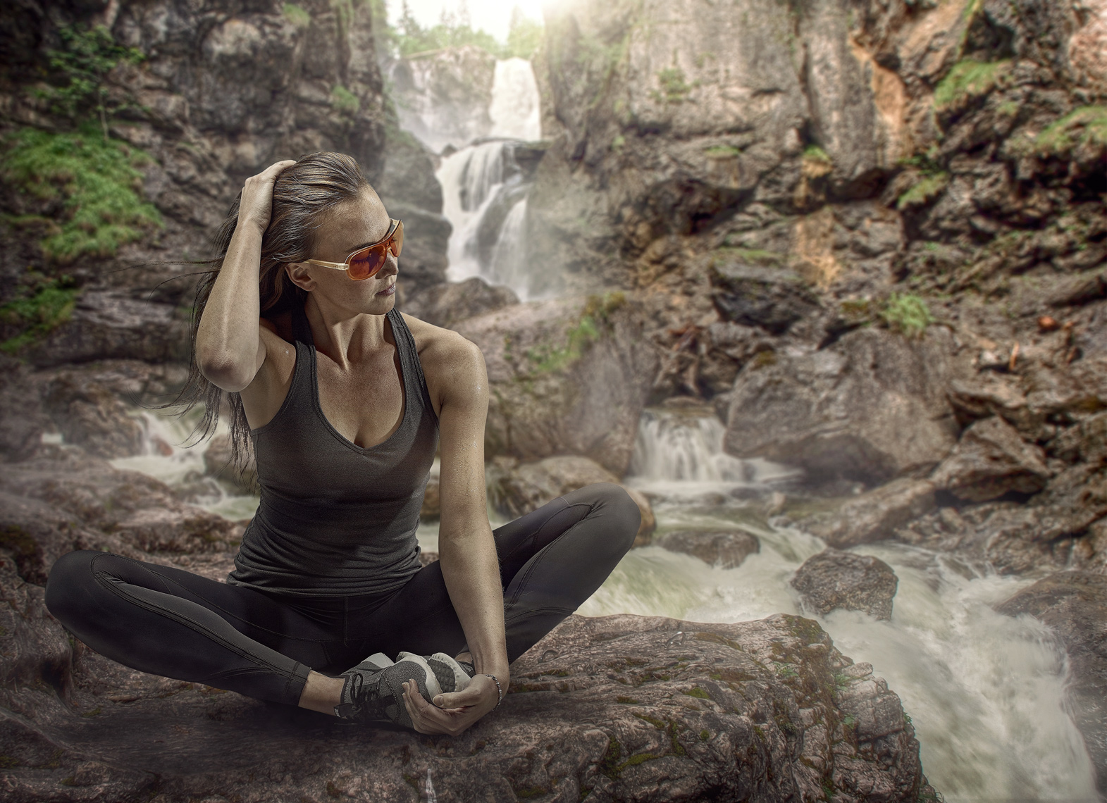 female hiker stretching on mountain trail with waterfall